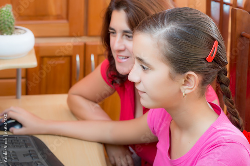 Hispanic girl and her young mother working on a computer