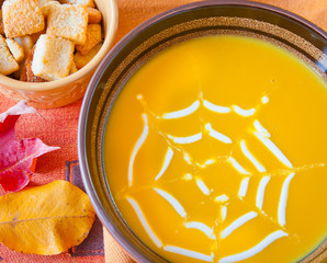 Pumpkin soup in a bowl decorated with spider web for Halloween.