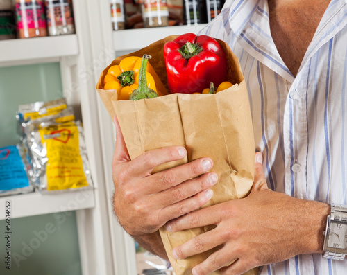 Man Holding Bag Of Vegetables In Store