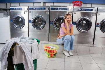 Beautiful Woman Using Mobile Phone At Laundry