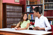 Librarian Looking At Schoolgirl While Sitting With Books In Libr