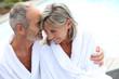 Happy senior couple in bathrobe by resort pool