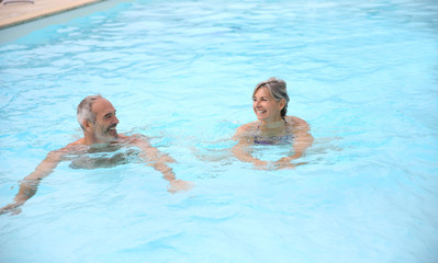 Active senior couple in resort pool