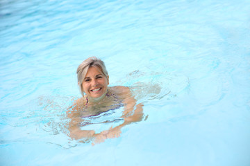 Cheerful senior woman in swimming-pool