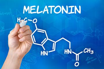 Hand mit Stift zeichnet chemische Strukturformel von Melatonin