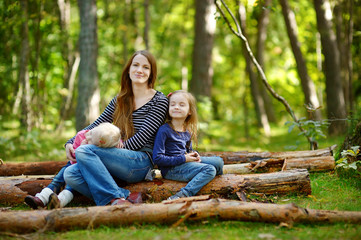 Two sisters and their mother sitting on a big log