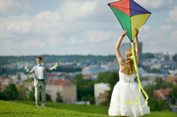 Bride and groom flying a kite on a wedding day