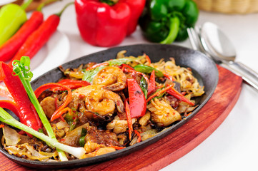 Spicy fried seafood on a hot pan.