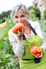 Senior woman tasting fresh tomatoes from garden