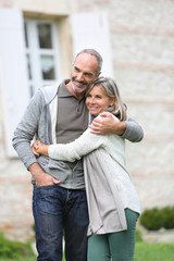 Cheerful mature couple walking in garden