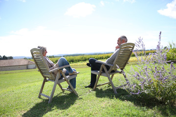 Senior people relaxing in long chairs in countryside