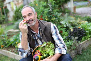 Mature man in garden smelling vegetable's aromas