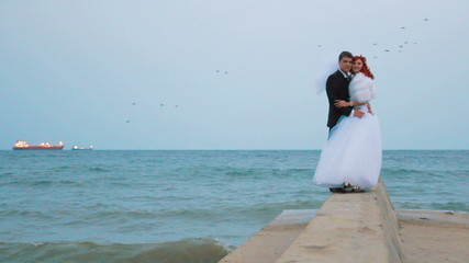 Bride and groom posing near the sea