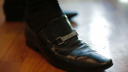 Man putting on his leather shoes. Close-up