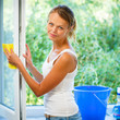 Pretty, young woman doing house work - washing windows