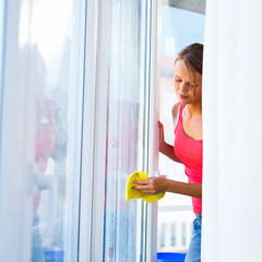 Pretty, young woman doing house work - washing windows