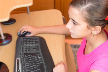 Young hispanic girl working on a computer at home