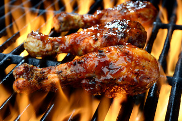grilling chicken on barbecue with flames