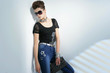 portrait of young woman wearing sunglasses holding purse