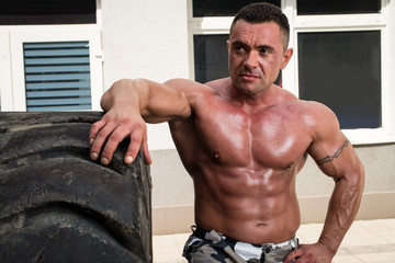 Bodybuilder Resting After Turning Tires