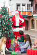 Children With Presents Looking At Santa Claus