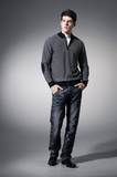 Portrait of a casual young in jeans satisfied man