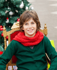 Boy Sitting On Chair Against Christmas Tree