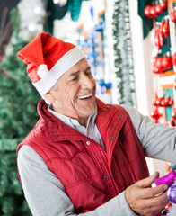 Owner In Santa Hat Working At Christmas Store