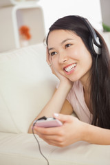 Happy asian girl lying on the sofa and listening to music with s
