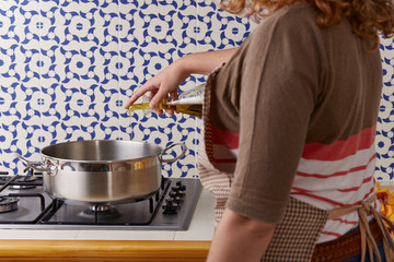 Young woman's hand pouring oil on a pan