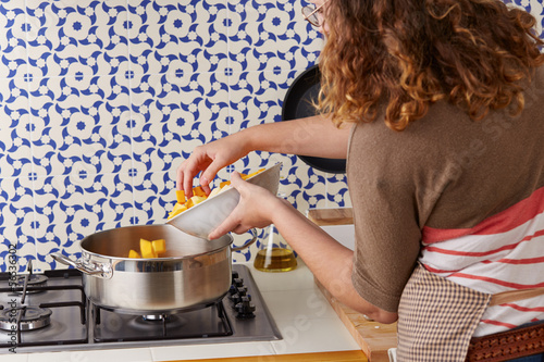 Young woman pouring vegetables on a pan