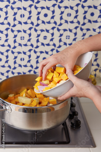 Hand pouring cut vegetables on a pan