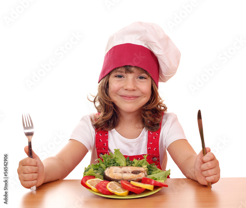 little girl cook with salmon seafood on table