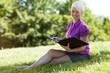 Smiling blond woman sitting in a park