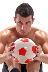 Jugador de fútbol sujetando un balón,entrenamiento.