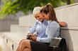 Two Businesswoman sitting outside while looking at a tablet