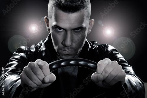 Hombre conduciendo un automóvil sujetando un volante.