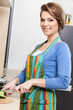 Attractive woman in striped apron chops vegetables