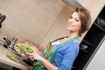 Woman in striped apron cuts vegetables in the kitchen