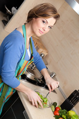 Attractive woman in striped apron cuts vegetables in the kitchen
