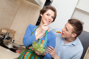 Woman offers her husband to taste salad with vegetables