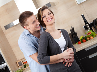Couple embraces one another in the kitchen