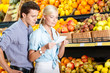 Happy couple with shopping list against the piles of fruits