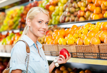 Girl at the shopping center choosing fruits and vegetables