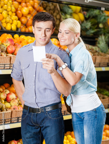 Happy couple with shopping list against the heaps of fruits