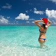Woman in santa's hat at beach