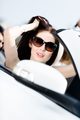 Close up of pretty female driver in the white convertible car