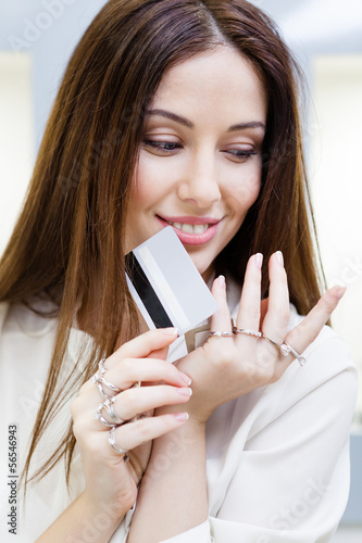 Woman with lots of rings on hands keeps credit card