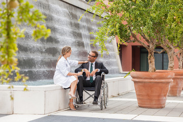 Smiling Businessman on wheelchair looking towards his doctor