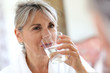 Leinwandbild Motiv Senior woman drinking water in the morning